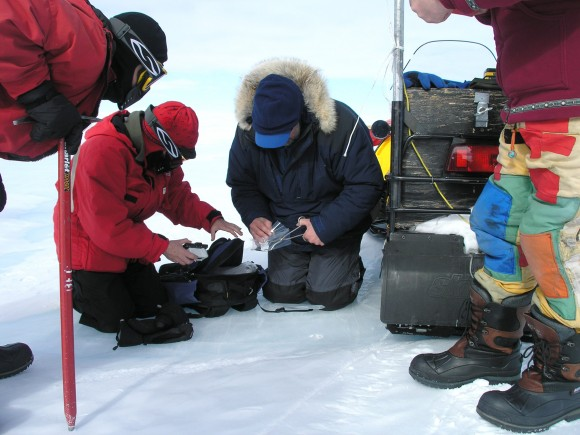 Team members gather to inspect and collect a meteorite being placed in a Teflon bag.  Photo credit: M. Keiding, 2007