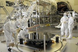 Engineers from Ball Aerospace inspect the first James Webb Space Telescope mirror segment upon its arrival at Marshall Space Flight Center, Huntsville, Al. for cryogenic testing. Credit: NASA