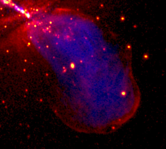  The image shows in red the X-ray emission produced by high-energy particles accelerated at the shock front where Centaurus A&#039;s expanding radio lobe (shown in blue) collides with the surrounding galaxy. (In the top-left corner X-ray emission from close to the central black hole, and from the X-ray jet extending in the opposite direction can also be seen.) Credit: NASA