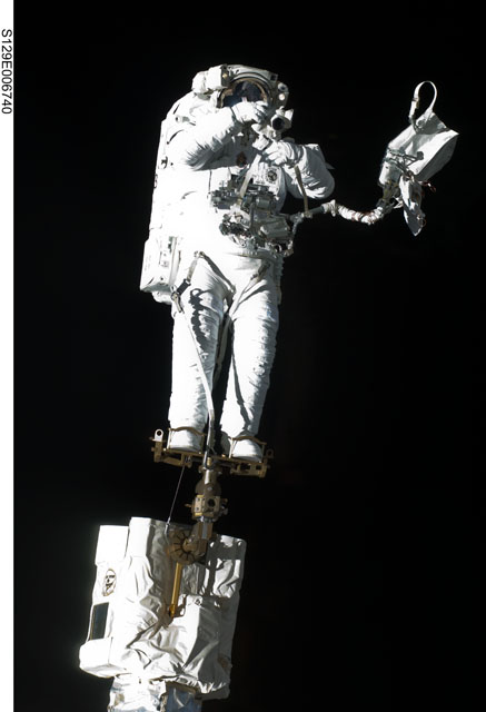Robert Satcher on the Canadarm2 during the first space walk of STS-129. Credit: NASA