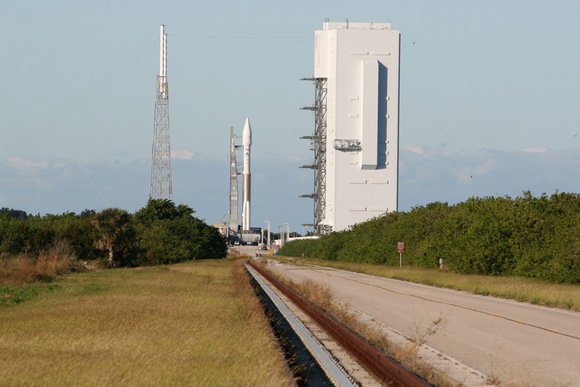 Atlas 5 rocket sits atop mobile launch platform at launch pad at Complex 41, Cape Canaveral, Florida on a cloudless day just a few hours prior to the scheduled post midnight launch on 14 November  2009.  Note lightings masts at left and Vertical Integration Facility at right where rocket components are assembled.  Credit: Ken Kremer