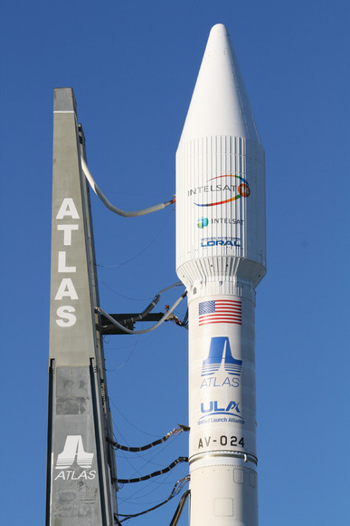 The Atlas 5 will orbit the commercial Intelsat 14 communications satellite.  This photo shows upper portion of rocket and umbilical cord connections leading from mobile launch platform to the decaled 4 meter wide white colored payload fairing and Centaur upper stage.  The flight is designated as tail number AV-024.   Credit: Ken Kremer