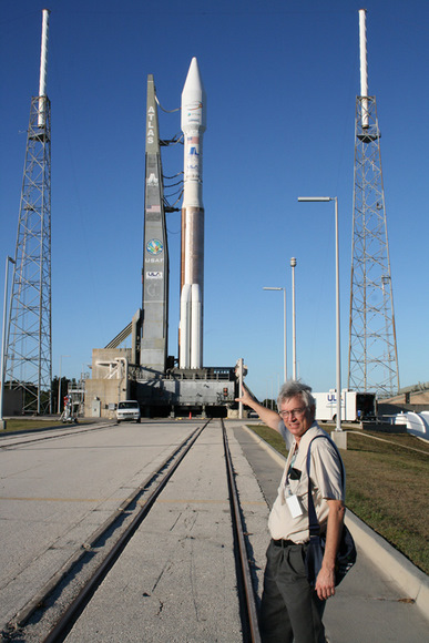 Ken Kremer with the Atlas launch vehicle at Pad 41 which will fly in the 431 configuration with 3 solid rocket boosters attached to the first stage and a single engine white colored Centaur upper stage. The Atlas 5 was rolled out to launch pad on Nov 12. Note tracks at center. The Intelsat satellite is encapsulated in a 4 meter wide extra extended payload fairing.  A similar Centaur stage impacted the moon as part of the LCROSS mission.