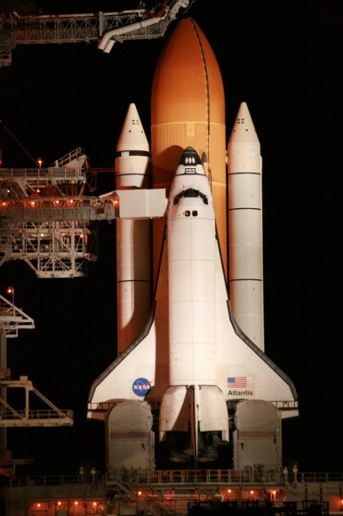 Close up of Space Shuttle Atlantis and crew walk out arm and platform at 195 ft level of pad 39 A.  Close out crew assists crew into their seats. Thereafter the orbiter hatch is closed for the 11 day mission to the ISS.  The arm swings away a few minutes prior to launch.   Credit: Ken Kremer  