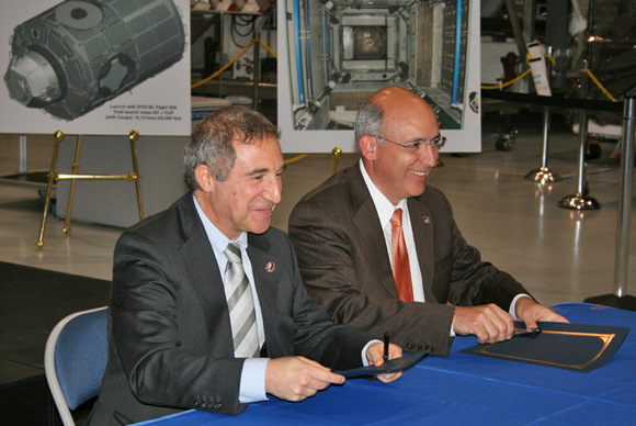 Bernardo Patti (left), the ESA space station manager for ESA and Michael Suffredini (right), the NASA space station manager sign Tranquility module ownership transfer documents inside the Space Station Processing Facility (SSPF) on 20 November 2009. Credit: Ken Kremer