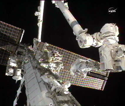 Image above: Expedition 24 Flight Engineers Doug Wheelock (right) and Tracy Caldwell Dyson work to replace a failed ammonia pump module outside of the International Space Station. Credit: NASA TV