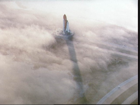 Two views of the Challenger being rolled out to pad 39A in the fog STS-6