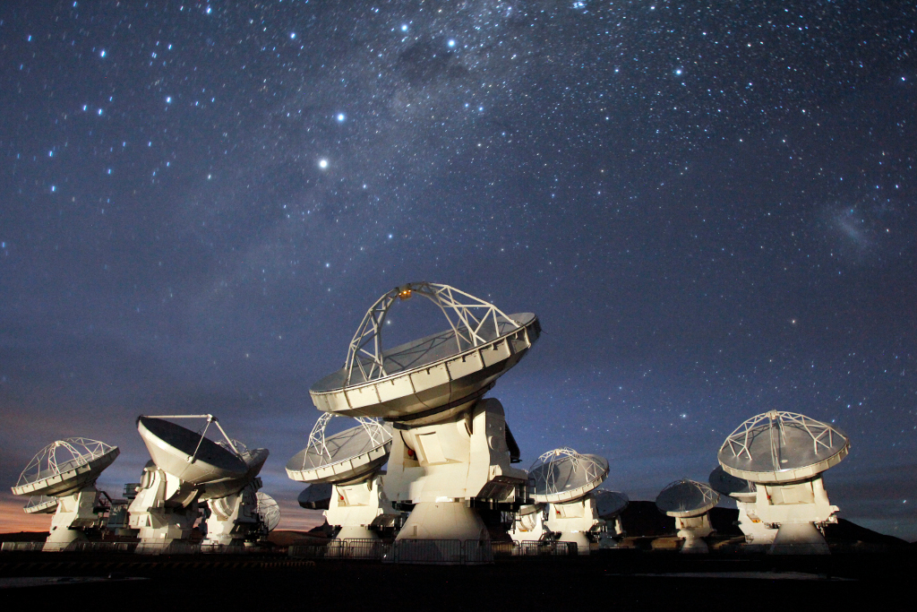 The Southern Cross, the Milky Way, and the Large Magellanic Cloud shine above the Atacama Large Millimeter/submillimeter Array (ALMA) as it observes on a clear night sky during its Early Science phase.  Image credit: C. Padilla, NRAO/AUI/NSF