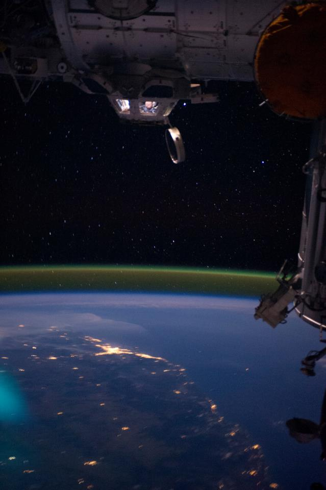 NASA astronaut Ron Garan looking down at a night view of Australia from the International Space Station's cupola..