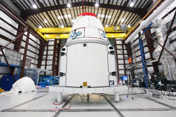SpaceX, Dragon spacecraft stands inside a processing hangar at Cape Canaveral Air Force Station in Florida. Teams had just installed the spacecraft&#039;s solar array fairings. Credit: NASA/Kim Shiflett