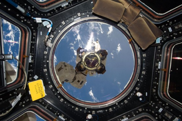 The end effector -- or grappler -- at the end of the Space Station's Canadarm 2 robotic arm is visible out the main window of the Cupola, with a view of our beautiful blue planet below. Credit: NASA.