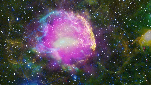 This multiwavelength composite shows the supernova remnant IC 443, also known as the Jellyfish Nebula. Fermi GeV gamma-ray emission is shown in magenta, optical wavelengths as yellow, and infrared data from NASA's Wide-field Infrared Survey Explorer (WISE) mission is shown as blue (3.4 microns), cyan (4.6 microns), green (12 microns) and red (22 microns). Cyan loops indicate where the remnant is interacting with a dense cloud of interstellar gas. Credit: NASA/DOE/Fermi LAT C