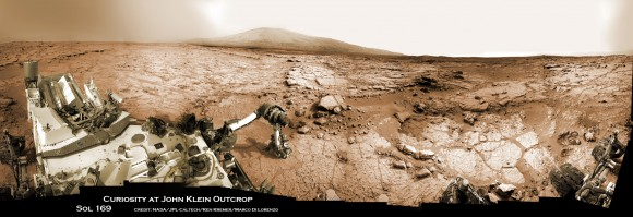 Curiosity accomplished Historic 1st drilling into Martian rock at John Klein outcrop on Feb 8, 2013 (Sol 182), shown in this context mosaic view of the Yellowknife Bay basin taken on Jan. 26 (Sol 169). The robotic arm is pressing down on the surface at John Klein outcrop of veined hydrated minerals - dramatically back dropped with  her ultimate destination; Mount Sharp.  Credit: NASA/JPL-Caltech/Ken Kremer/Marco Di Lorenzo