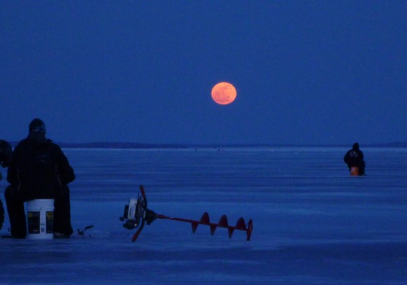 Fishing for walleye on the Bay of Quinte (Lake Ontario) near Belleville, Ontario, when the full Moon appeared through the clouds on the horizon. Credit and copyright: Rick Stankiewicz.