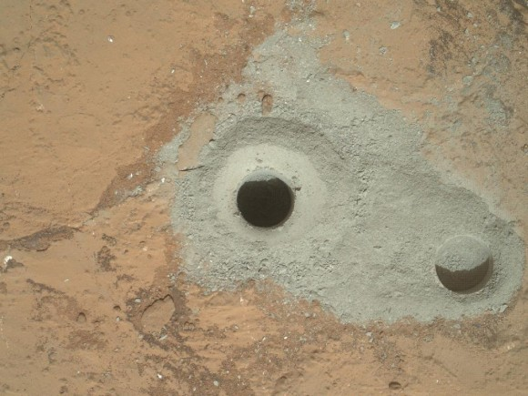 "Curiosity's First Sample Drilling hole is shown at the center of this image in a rock called ""John Klein"" on Feb. 8, 2013, or Sol 182 operations. The image was obtained by Curiosity's Mars Hand Lens Imager (MAHLI). The sample-collection hole is 0.63 inch (1.6 centimeters) in diameter and 2.5 inches (6.4 centimeters) deep. The ""mini drill"" test hole near it is the same diameter, with a depth of 0.8 inch (2 centimeters). Credit: NASA/JPL-Caltech/MSSS Read more: http://www.universetoday.com/99911/historic-mars-rock-drilling-sample-set-for-analysis-by-curiosity-robot-in-search-of-organics/#ixzz2Mu1y6Fpr"