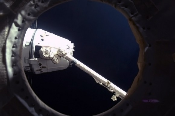 'Success! Canadarm2 holds Dragon by the nose, to drag it up and hook it on to a Station hatch.' Credit: NASA/Chris Hadfield.