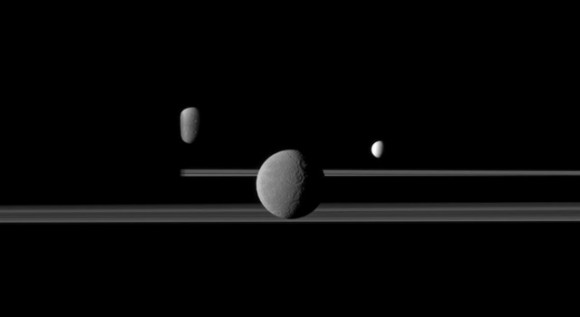 The Cassini spacecraft observes three of Saturn's moons set against the darkened night side of the planet. Credit: NASA/JPL/Space Science Institute