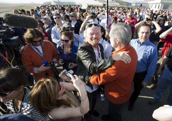 "Sir Richard Branson hugs designer Burt Rutan as they are surrounded by employee's of Virgin Galactic, The SpaceShip Company and Scaled Composites watch as Virgin Galactic's SpaceShip2 streaks across the sky under rocket power, its first ever since the program began in 2005. Burt's wife Tonya Rutan is at right taking their photo. The spacecraft was dropped from its ""mothership"", WhiteKnight2 over the Mojave, CA area, April 29, 2013 at high altitude before firing its hybrid power motor. Virgin Galactic hopes to become the first commercial space venture to bring multiple passengers into space on a regular basis."