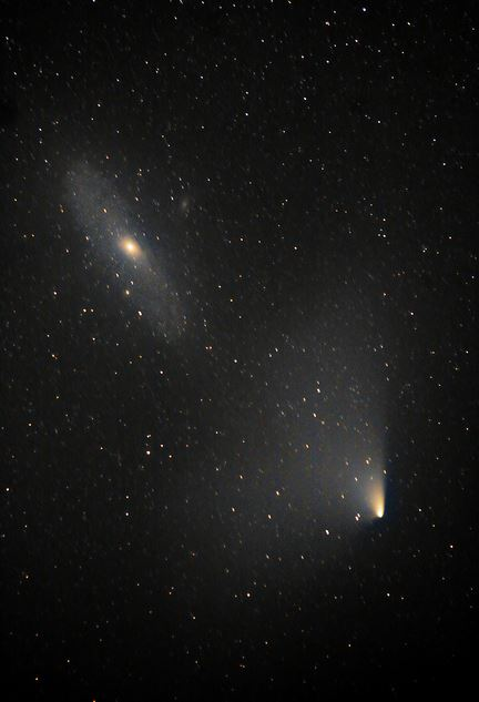 Two objects 2.5 million lightyears apart... PanSTARRS & Andromeda.  Credit and copyright: Brendan Alexander.