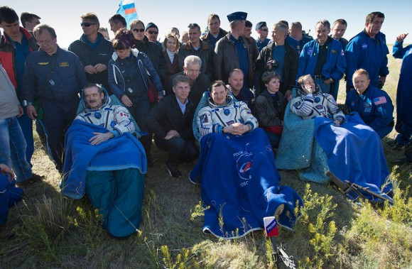 Expedition 35 Commander Chris Hadfield of the Canadian Space Agency (CSA), left, Russian Flight Engineer Roman Romanenko of the Russian Federal Space Agency (Roscosmos), center, and NASA Flight Engineer Tom Marshburn sit in chairs outside the Soyuz Capsule just minutes after they landed in a remote area outside the town of Dzhezkazgan, Kazakhstan, on Tuesday, May 14, 2013. Hadfield, Romanenko and Marshburn are returning from five months onboard the Internation