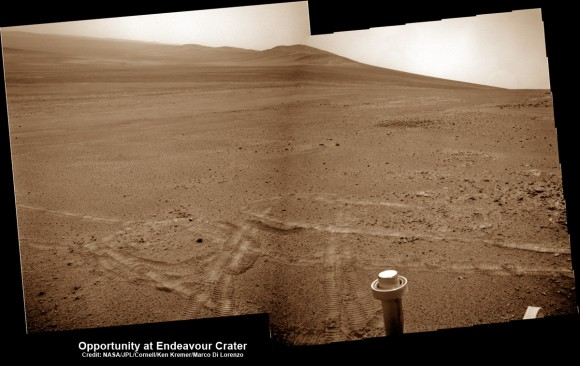 Opportunity pops a wheelie on May 15, 2013 (Sol 3308) and then made history by driving further to the mountain ahead on the next day, May 16 (Sol 3309), to establish a new American driving record for a vehicle on another world.  This navcam mosaic shows the view forward to Opportunitys future destinations of Solander Point and Cape Tribulation along the lengthy rim of huge Endeavour crater spanning 14 miles (22 km) in diameter.  Credit: NASA/JPL/Cornell/Kenneth Kremer/Marco Di Lorenzo.  