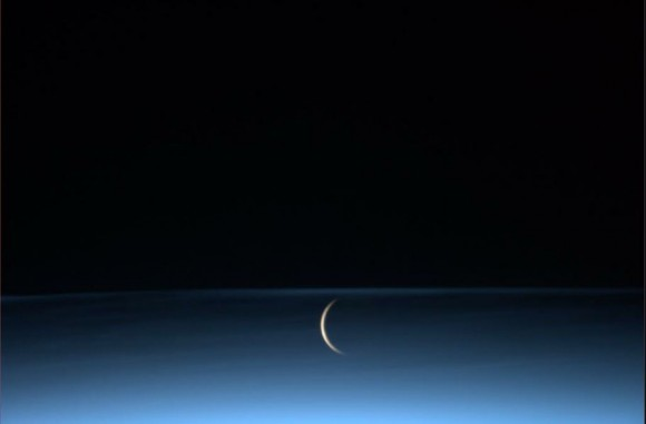 The Moon rises surrounded by noctilucent clouds, as seen from the Interna