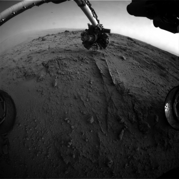 NASA's Mars rover Curiosity used a new technique, with added autonomy for the rover, in placement of the tool-bearing turret on its robotic arm during the 399th Martian day, or sol, of the mission. This image from the rover's front Hazard Avoidance Camera (Hazcam) on that sol shows the position of the turret during that process, with the Alpha Particle X-ray Spectrometer (APXS) instrument placed close to the target rock. Credit: NASA/JPL-Caltech