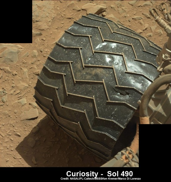 Up close view of hole in one of rover Curiosity's six wheels caused by recent driving over rough Martian rocks. Mosaic assembled from Mastc