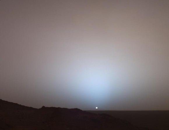 "A Moment Frozen in Time On May 19th, 2005, NASA's Mars Exploration Rover Spirit captured this stunning view as the Sun sank below the rim of Gusev crater on Mars. This Panoramic Camera (Pancam) mosaic was taken around 6:07 in the evening of Sol 489. The terrain in the foreground is the rock outcrop ""Jibsheet,"" a feature that Spirit has been investigating for several weeks (rover tracks are dimly visible leading up to ""Jibsheet""). The floor of Gusev crater is visible in the distance, and the Sun is setting behind the wall of Gusev some 80 km (50 miles) in the distance. Credit: NASA/JPL-Caltech/Texas A&M/Cornell"