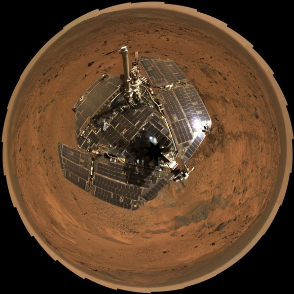 This bird's-eye view from August 2005 combines a self-portrait of the spacecraft deck and a panoramic mosaic of the Martian surface as viewed by NASA's Mars Exploration Rover Spirit. The rover's solar panels are still gleaming in the sunlight, having acquired only a thin veneer of dust two years after the rov