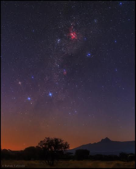 At the break of dawn the southern Milky Way is photographed over Mount Kilimanjaro, as seen from Amboseli National Park, Kenya. The Great Carina Nebula is the red cloud at top. Constellation Crux or the Southern Cross appear on the left. On the Earth is the second peak of Mount Kilimanjaro reaching 5149 m high, known as Mawenz