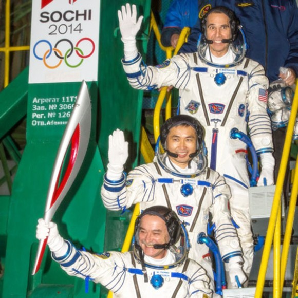 Expedition 38 Soyuz Commander Mikhail Tyurin, holding the Olympic torch, and Flight Engineers Koichi Wakata and Rick Mastracchio wave farewell prior to boarding the Soyuz TMA-11M rocket for launch. (NASA/Bill Ingalls)