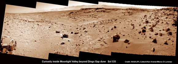 "Curiosity scans Moonlight Valley beyond Dingo Gap Dune. Curiosity's view to ""Moonlight Valley"" beyond after crossing over 'Dingo Gap' sand dune. This photomosaic was taken after Curiosity drove over the 1 meter tall Dingo Gap sand dune and shows dramatic scenery in the valley beyond, back dropped by eroded rim of Gale Crater. Assembled from navigation camera (navcam) raw images from Sol 535 (Feb. 6, 2104) Credit: NASA/JPL-Caltech/Ken Kremer- kenkremer.com/Marco Di Lorenzo"