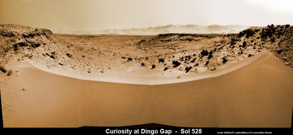 Curiosity's View Past Tall Dune at edge of 'Dingo Gap'  This photomosaic from Curiosity's Navigation Camera (Navcam) taken at the edge of the entrance to the Dingo Gap shows a 3 foot (1 meter) tall dune and valley terrain beyond to the west, all dramatically back dropped by eroded rim of Gale Crater. View from the rover's current position on Sol 528 (Jan. 30, 2014). The rover team may decide soon whether Curiosity will bridge the dune gap as a smoother path