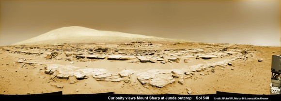 Martian landscape scene with rows of striated rocks in the foreground and Mount Sharp on the horizon. NASA's Curiosity Mars rover paused mid drive at the Junda outcrop to snap the images for this navcam camera photomosaic on Sol 548 (Feb. 19, 2014) and then continued traveling southwards towards mountain base.    Credit: NASA/JPL-Caltech/Marco Di Lorenzo/Ken Kremer-kenkremer.com