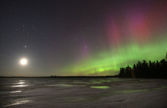 Auroral arcs are topped by red rays light up the northeast while the moon and Jupiter shine off to the west in this photo taken last night over a small lake north of Duluth, Minn. Both moon and aurora light are reflected in puddles on the ice. Credit: Bob King