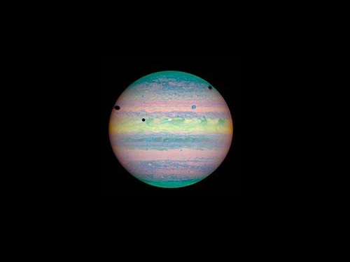 Hubble nabs a triple shadow transit in this false color image taken in 2004. Credit: NASA/HST.