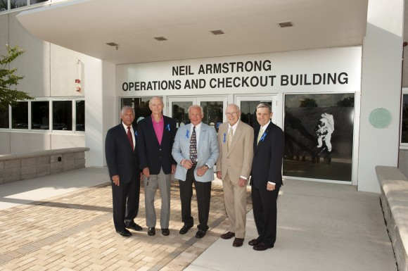 At the Kennedy Space Center in Florida on July 21, 2014, NASA officials and Apollo astronauts have a group portrait taken in front of the refurbished Operations and Checkout Building, newly named for Apollo 11 astronaut Neil Armstrong, the first person to set foot on the moon. From left are NASA Administrator Charles Bolden, Apollo astronauts Mike Collins, Buzz Aldrin and Jim Lovell, and Center Director Robert Cabana. The visit of the former astronauts was part of NASA's 45th anniversary celebration of the Apollo 11 moon landing. The building's high bay is being used to support the agency's new Orion spacecraft, which will lift off atop the Space Launch System rocket. Photo credit: NASA/Kevin O'Connell