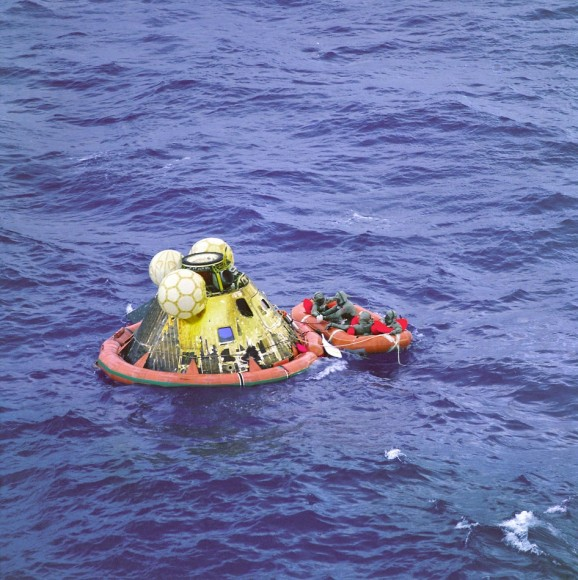 Apollo 11 Comes Home. The Apollo 11 crew await pickup by a helicopter from the USS Hornet, prime recovery ship for the historic lunar landing mission. The fourth man in the life raft is a United States Navy underwater demolition team swimmer. All four men are wearing biological isolation garments.  The splashed down at 12:49 a.m. EDT, July 24, 1969, about 812 nautical miles southwest of Hawaii and only 12 nautical miles from the USS Hornet. Credit: NASA