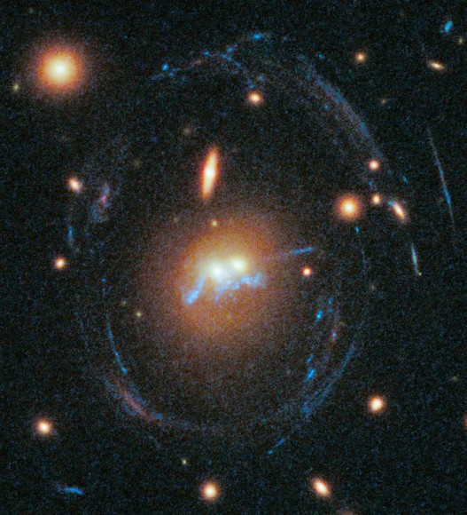 "In this new Hubble image shows two galaxies (yellow, center) from the cluster SDSS J1531+3414 have been found to be merging into one and a ""chain"" of young stellar super-clusters are seen winding around the galaxies's nuclei. The galaxies are surrounded by an egg-shaped blue ring caused by the immense gravity of the cluster bending light from other galaxies beyond it. Credit: NASA/ESA/Grant Tremblay"