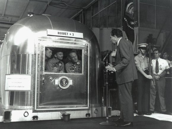 "President Nixon Greets the Returning Apollo 11 Astronauts. The Apollo 11 astronauts, left to right, Commander Neil A. Armstrong, Command Module Pilot Michael Collins and Lunar Module Pilot Edwin E. ""Buzz"" Aldrin Jr., inside the Mobile Quarantine Facility aboard the USS Hornet, listen to President Richard M. Nixon on July 24, 1969 as he welcomes them back to Earth and congratulates them on"