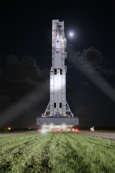 This artist concept shows NASA's Space Launch System, or SLS, rolling to a launch pad at Kennedy Space Center at night. SLS will be the most powerful rocket in history, and the flexible, evolvable design of this advanced, heavy-lift launch vehicle will meet a variety of crew and cargo mission needs.   Credit:  NASA/MSFC