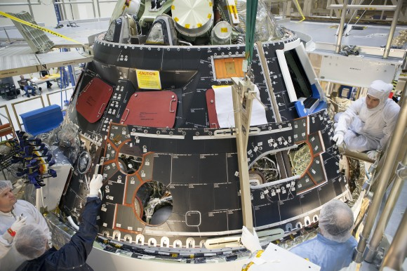 Inside the Operations and Checkout Building high bay at NASA's Kennedy Space Center in Florida, technicians dressed in clean-room suits install a back shell tile panel onto the Orion crew module.  Credit: NASA/Dimitri Gerondidakis