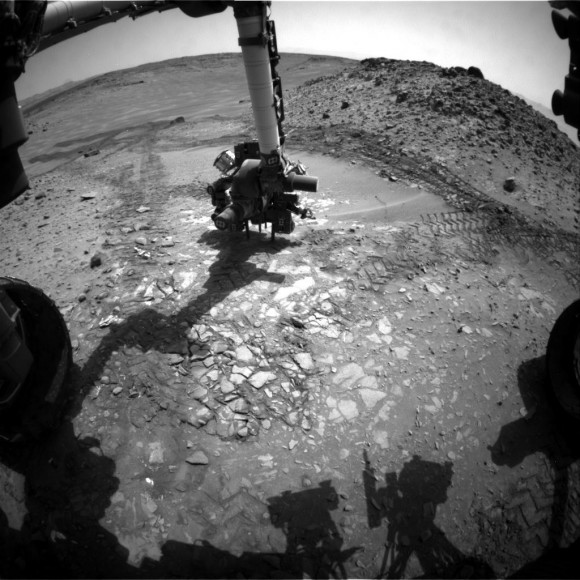 """This image from the front Hazcam on NASA's Curiosity Mars rover shows the rover's drill in place during a test of whether the rock beneath it, """"Bonanza King,"""" would be an acceptable target for drilli"""