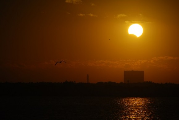 The Partially eclipsed Sun rising over the Vehicle Assembly Building on the Florida Space Coast on November 3rd, 2013.