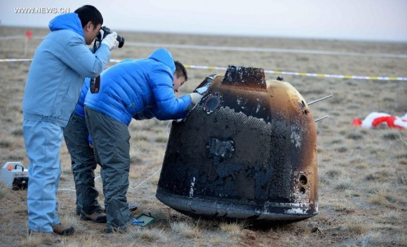 Researchers retrieve the return capsule of China's unmanned lunar orbiter in the central region of north China's Inner Mongolia Autonomous Region, Nov. 1, 2014. Return capsule of China's test lunar orbiter landed successfully early Saturday morning in north China's Inner Mongolia Autonomous Region, according to the Beijing Aerospace Control Center.  Credit: Xinhua/Ren Junchuan