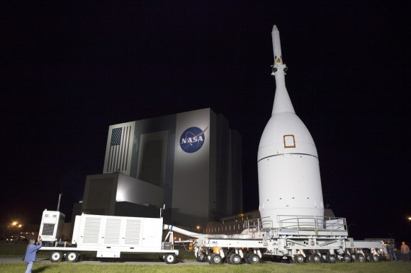 At NASA's Kennedy Space Center in Florida, the agency's Orion spacecraft pauses in front of the spaceport's iconic Vehicle Assembly Building as it is transported to Launch Complex 37 at Cape Canaveral Air Force Station. After arrival at the launch pad, United Launch Alliance engineers and technicians will lift Orion and mount it atop its Delta IV Heavy rocket. Credit:   NASA/Frankie Martin