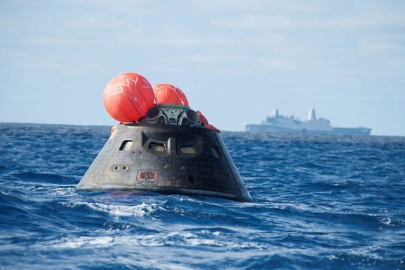 Orion crew module after splash down in the Pacific Ocean with the Crew Module Uprighting System bags deployed and the USS Anchorage in the background that concludes its first test flight on the EFT-1 mission on Dec. 5, 2014.  Credit: U.S. Navy