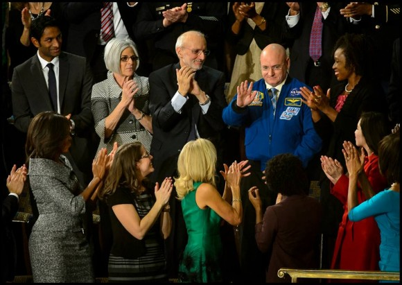 NASA astronaut Scott Kelly stands as he is recognized by President Barack Obama, while First lady Michelle Obama, front left, and other guest applaud, during the State of the Union address on Capitol Hill in Washington, Tuesday Jan. 20, 2015. This March, Astronaut Scott Kelly will launch to the International Space Station and become the first American to live and work aboard the orbiting laboratory for a year-long mission. Credit: NASA/Bill Ingalls