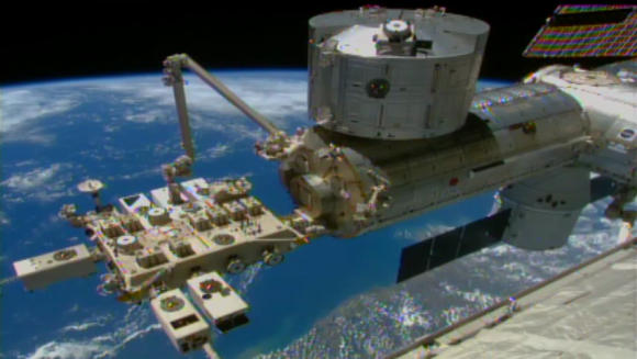 This video frame shows a robotic arm on the space station, called the Japanese Experiment Module Remote Manipulator System, successfully installing NASA's Cloud-Aerosol Transport System (CATS) to the Space Station's Japanese Experiment Module on Jan. 22, 2015.  Credit: NASA